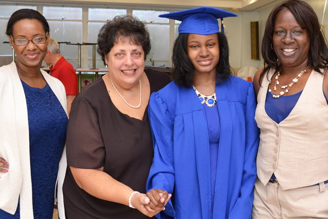 three women with student in graduation gown