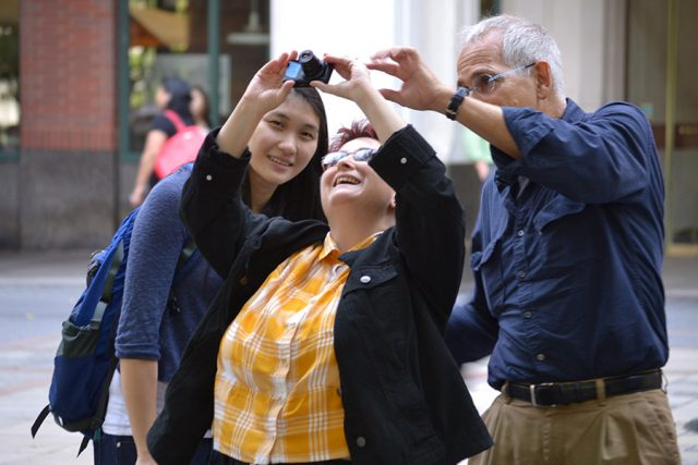 three people taking photo outside