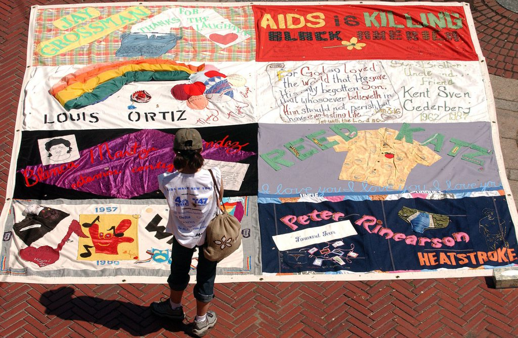 person looking at large aids quilt